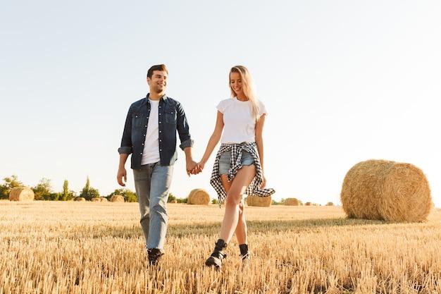 Foto de um jovem casal caminhando pelo campo dourado, com montes de feno durante um dia ensolarado