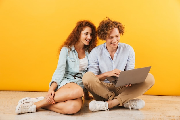 Foto de um jovem casal de conteúdo, homem e mulher, sentado no chão e usando um laptop prateado, isolado sobre um fundo amarelo