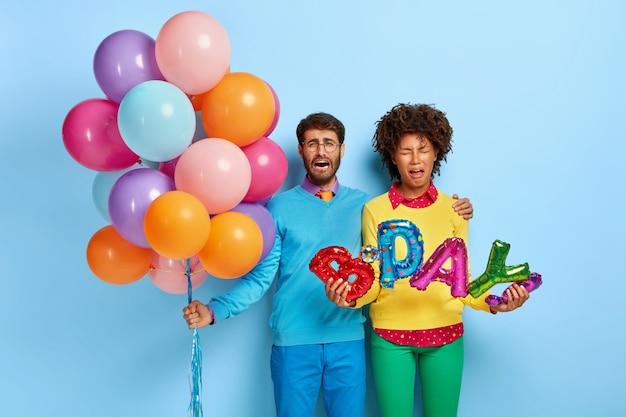 Foto de um jovem casal descontente em uma festa posando com balões