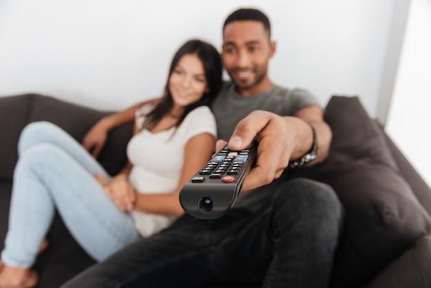 Foto de um jovem casal feliz abraçando e assistindo tv no sofá em casa. foco disponível com controle remoto.