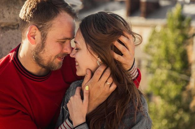 Foto de um jovem casal feliz ao pôr do sol. relacionamento feliz. um homem e uma mulher estão se abraçando sob o sol. amantes e o sol.