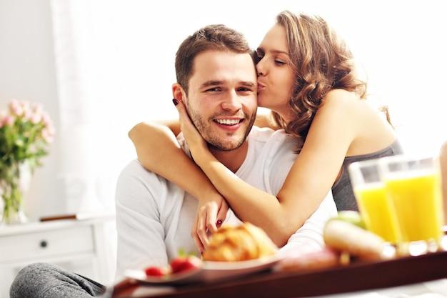 Foto de um jovem casal tomando café da manhã na cama