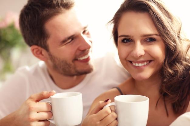 Foto de um jovem casal tomando café na cama