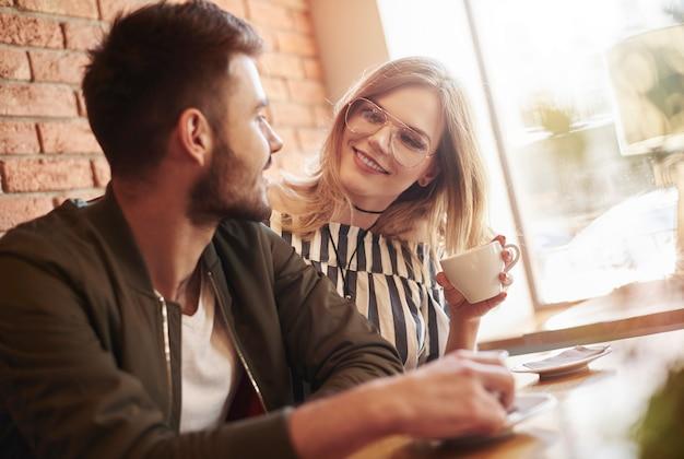 Foto de um jovem casal tomando uma xícara de café