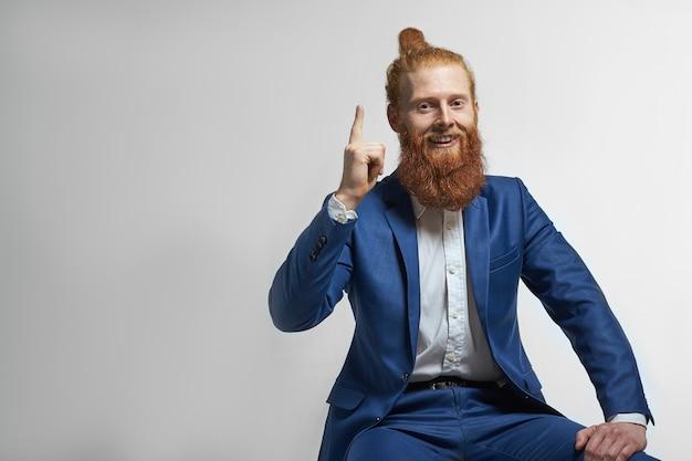 Foto de um jovem ceo elegante e confiante com um nó de cabelo e uma espessa barba ruiva sorrindo alegremente apontando para cima, sentado contra o fundo da parede do estúdio em branco com espaço de cópia para sua informação