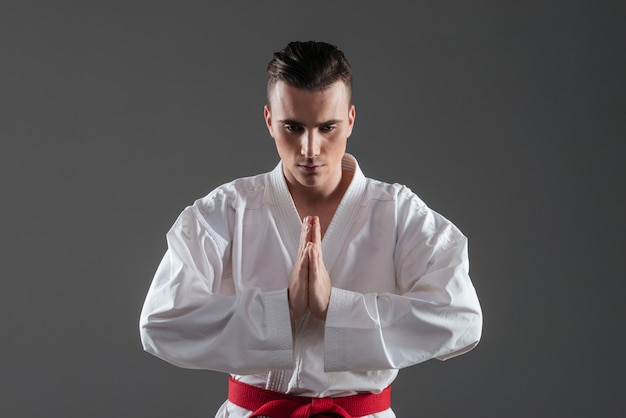 Foto de um jovem desportista bonito vestido de quimono, gesticulando com as mãos sobre um fundo cinza. olhando para baixo.