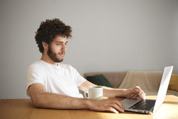 Foto de um jovem elegante e atraente com barba difusa sorrindo assistindo séries online ou navegando na internet usando wi-fi em seu laptop genérico, sentado na mesa de madeira com a caneca, tomando café ou chá