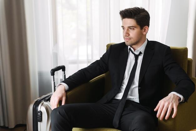 Foto de um jovem empresário calmante vestindo um terno preto, olhando para o lado e sentado na poltrona com uma mala em um apartamento de hotel