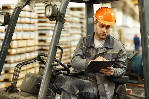 Foto de um jovem engenheiro barbudo preenchendo documentos sentado