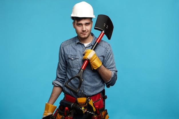 Foto de um jovem escavador usando luvas, capacete branco e cinto de ferramentas carregando uma pá