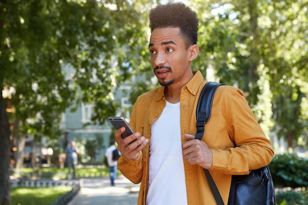 Foto de um jovem espantado de cara de pele escura em camisa amarela caminhando no parque, segurando o telefone, ouve notícias inacreditáveis, com boca e olhos bem abertos, parece atordoado.