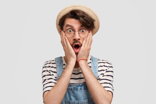 Foto de um jovem fazendeiro barbudo atordoado mantém as palmas das mãos nas bochechas, ouve más notícias sobre a situação na fazenda, vestido com uma camiseta listrada branca e overllas jeans, isolado sobre a parede branca