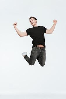 Foto de um jovem feliz vestido com uma camiseta preta, pulando sobre um fundo branco, olhando de lado.