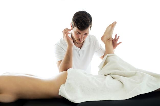 Foto de um jovem fisioterapeuta fazendo um tratamento nas costas de um paciente em uma sala de fisioterapia. reabilitação, massagem médica e conceito de terapia manual.