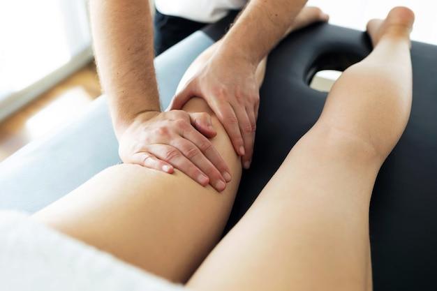 Foto de um jovem fisioterapeuta fazendo um tratamento nas pernas de um paciente em uma sala de fisioterapia. reabilitação, massagem médica e conceito de terapia manual.