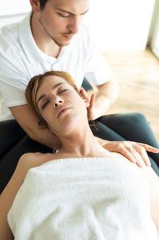 Foto de um jovem fisioterapeuta fazendo um tratamento no pescoço de um paciente em uma sala de fisioterapia. reabilitação, massagem médica e conceito de terapia manual.