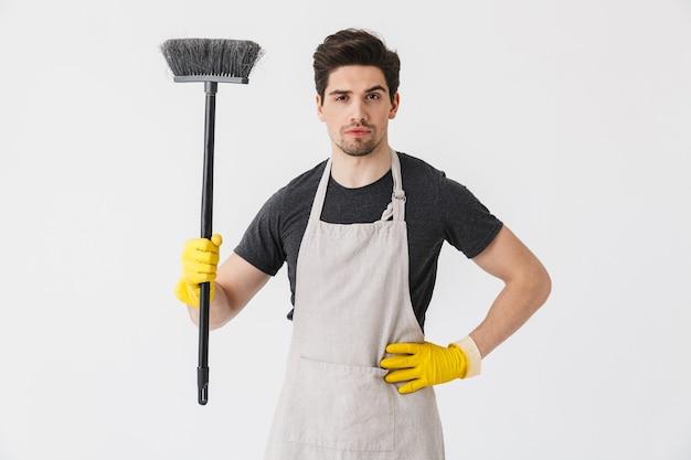 Foto de um jovem forte usando luvas de borracha amarelas para proteger as mãos segurando uma vassoura enquanto limpa a casa isolada sobre o branco
