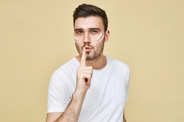Foto de um jovem homem bonito e confiante em uma camiseta branca, mantendo o dedo indicador nos lábios, como se estivesse explodindo com uma arma após atirar, fazendo sinal de silêncio sigilo e gesto de silêncio