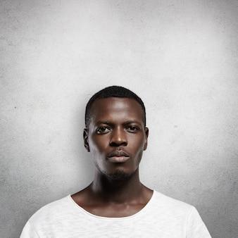 Foto de um jovem homem de pele escura, sério e confiante, isolado contra uma parede cinza