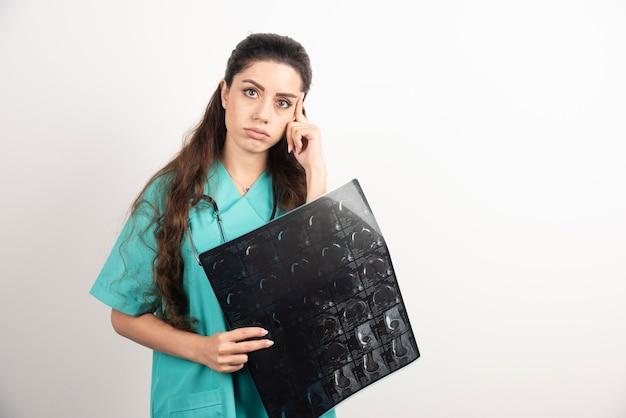 Foto de um jovem médico segurando um raio-x sobre uma parede branca.