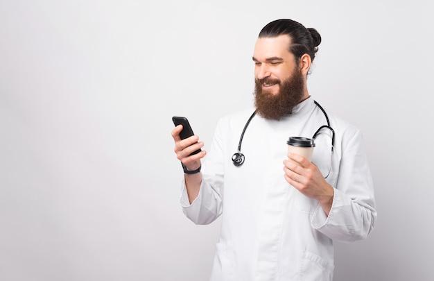 Foto de um jovem médico sorridente e alegre usando o smartphone e segurando uma xícara de café de papel