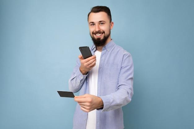 Foto de um jovem moreno sorridente e atraente, com a barba por fazer, vestindo uma camisa azul casual e
