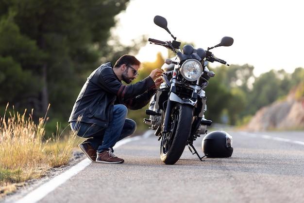 Foto de um jovem motociclista verificando sua moto antes de dirigi-la na estrada.