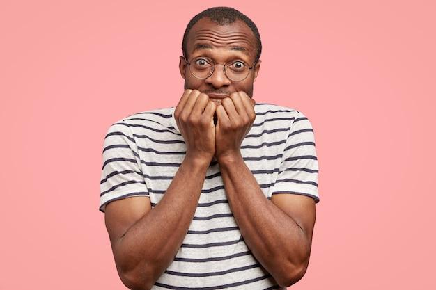 Foto de um jovem negro ansioso que morde as unhas com expressão preocupada