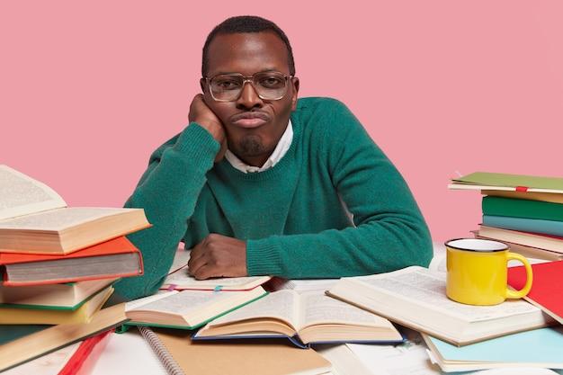 Foto de um jovem negro infeliz mantém a mão sob o queixo, franze os lábios, usa óculos óticos, sente-se solitário, lê livros