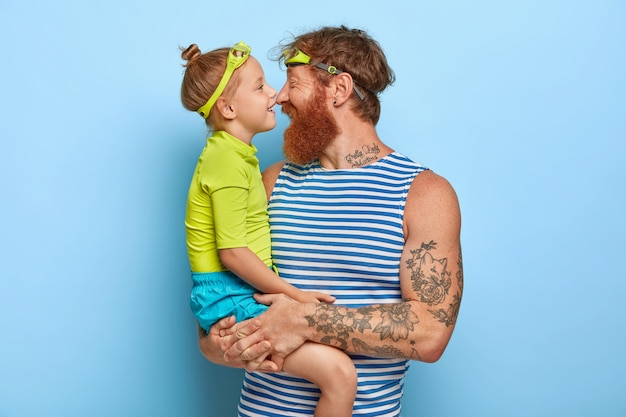Foto de um jovem ruivo barbudo carrega a filha pequena, toca o nariz e tem expressões felizes, usa óculos de proteção, entra na piscina para passar o dia ativamente, expressa amor um ao outro.
