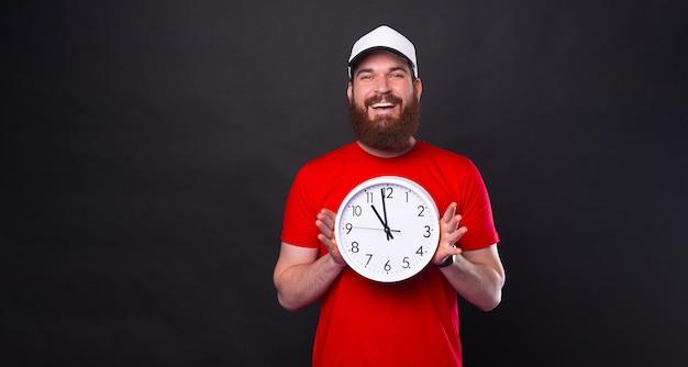 Foto de um jovem sorridente com barba em uma camiseta vermelha mostrando um grande relógio de parede sobre fundo preto
