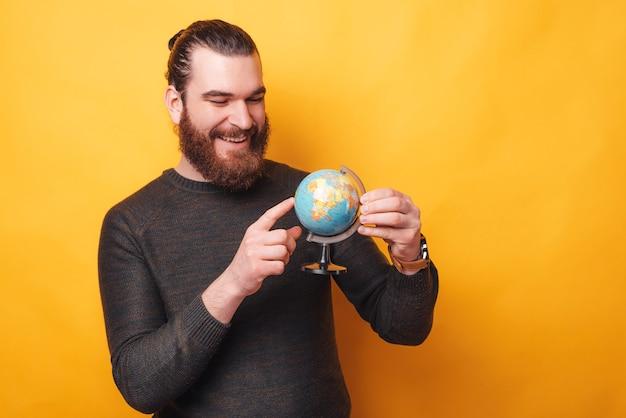 Foto de um jovem sorrindo e olhando para um globo perto de uma parede amarela