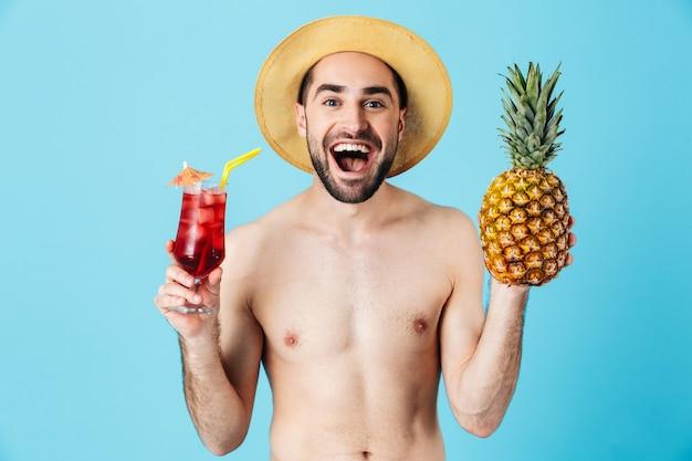 Foto de um jovem turista sem camisa usando chapéu de palha e sorrindo enquanto segura abacaxi e coquetel isolados