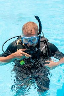Foto de um jovem usando uma máscara de mergulho com snorkel em uma piscina