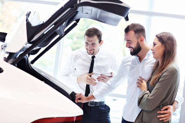 Foto de um jovem vendedor confiante explicando todas as características do carro para os jovens proprietários atraentes