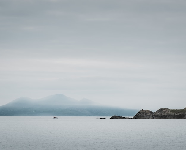 Foto de um lago e penhascos, montanhas enevoadas