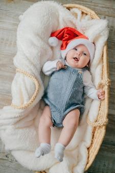 Foto de um lindo bebê recém-nascido com o boné de natal do papai noel e sorrisos