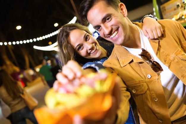 Foto de um lindo casal atraente comendo batatas juntos em comer mercado na rua.