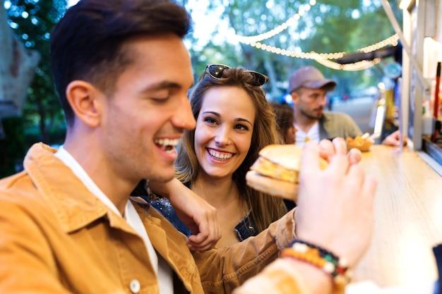 Foto de um lindo casal atraente, compartilhando e comendo hambúrguer juntos em comer mercado na rua.