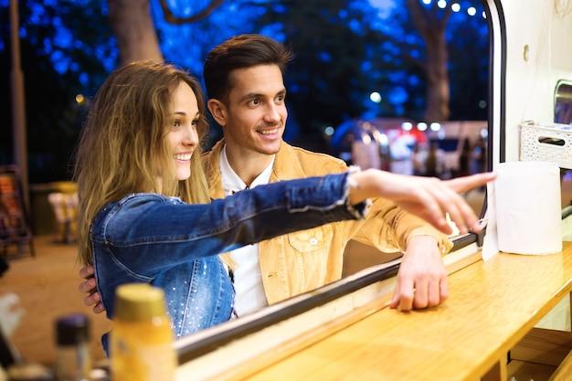 Foto de um lindo casal atraente, escolhendo e comprando diferentes tipos de fast food em comer mercado na rua.