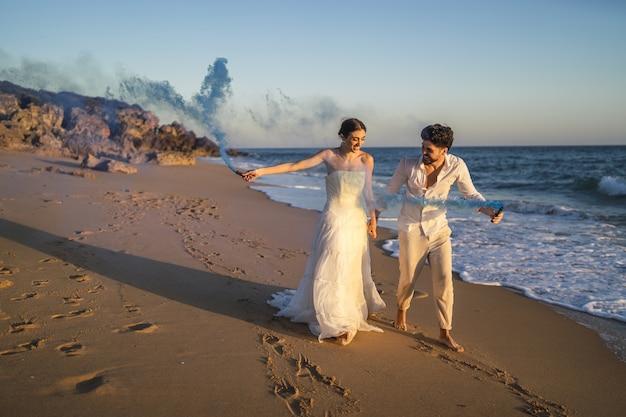 Foto de um lindo casal posando com uma bomba de fumaça azul na praia