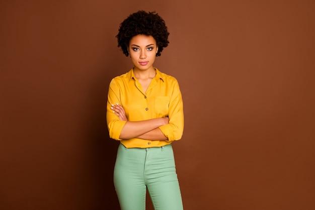 Foto de um lindo negócio, pele escura, senhora encaracolada, olhando estritamente colegas, mau humor, pessoa confiante, braços cruzados, usar camisa amarela, calça verde, isolada cor marrom