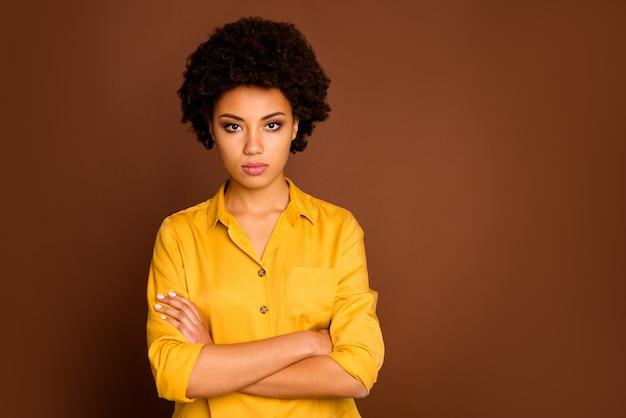 Foto de um lindo negócio, pele morena, cacheada, senhora, olhando estritamente, colegas, mau humor, pessoa confiante, trabalhador, usar camisa amarela, isolado, cor marrom