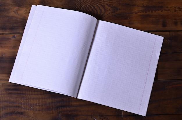 Foto de um livro de cheques branco limpo da escola em um fundo de madeira marrom. idéia ou conceito de mensagem.
