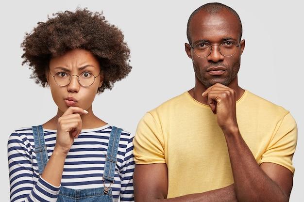 Foto de um marido afro-americano perplexo e sua esposa segurando o queixo e franzindo os lábios