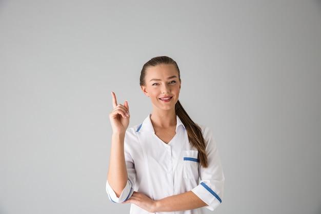 Foto de um médico cosmetologista bela jovem isolada sobre a parede cinza apontando.