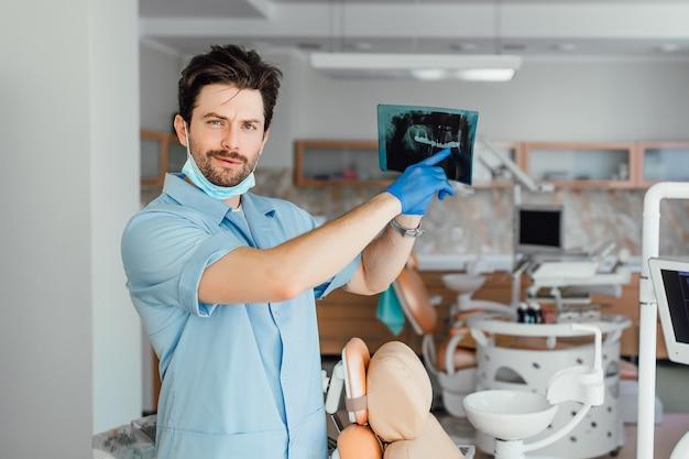 Foto de um médico ou dentista olhando para um raio-x, em seu escritório.