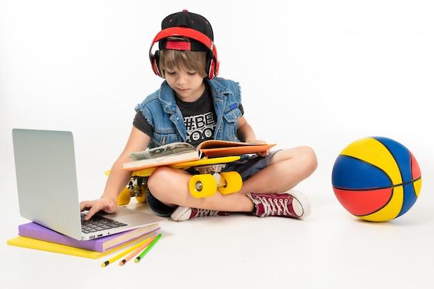Foto de um menino adolescente senta-se no chão em jaqueta jeans e shorts. tênis com centavo amarelo, fones de ouvido vermelhos, laptop, bola e jogar jogos de computador ou fazer lição de casa isolada