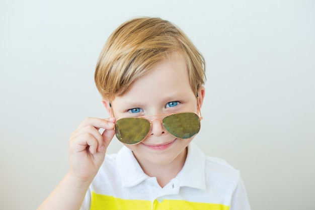 Foto de um menino lindo, olhando por cima de óculos de sol