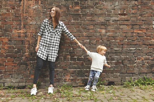 Foto de um menino loiro e uma jovem garota em uma caminhada perto da parede de tijolos. tipo minúsculo puxando uma tia adulta para ir embora. menina caucasiana de camisa xadrez fica teimosa. duas pessoas olhando para lados opostos.